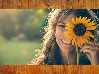 A woman looking at the camera, hiding one eye behind a sunflower.