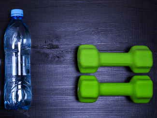 A photo of water and dumbbells representing to metabolism boosters: hydration and exercise.