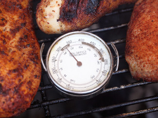 A grill with chicken and a thermometer.