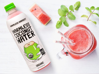 A glass of Watermelon Strawberry Basil Smoothie with a bottle of Harmless Harvest Coconut Water.